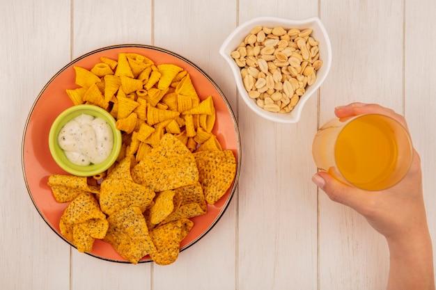 Bovenaanzicht van vrouwelijke hand met een glas sinaasappelsap met een oranje plaat van pittige knapperige chips met saus op een groene kom met pijnboompitten op een beige houten tafel