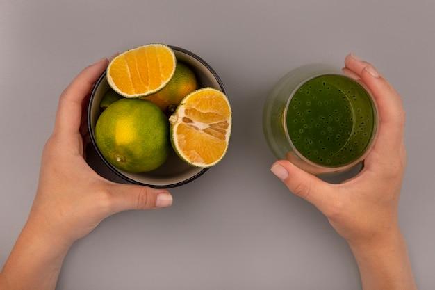 Bovenaanzicht van vrouwelijke hand met een glas vers kiwisap in de ene hand en in de andere hand een kom met mandarijnen