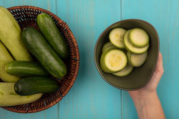 Bovenaanzicht van vrouwelijke hand met een kom verse gehakte courgettes met een emmer komkommers en courgettes op een blauwe houten muur