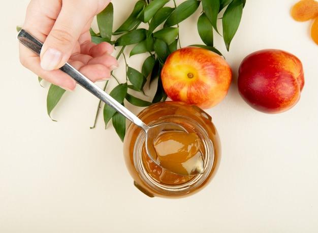 Bovenaanzicht van vrouwelijke hand met een lepel met perzik jam over de glazen pot en verse nectarines met groene bladeren op wit