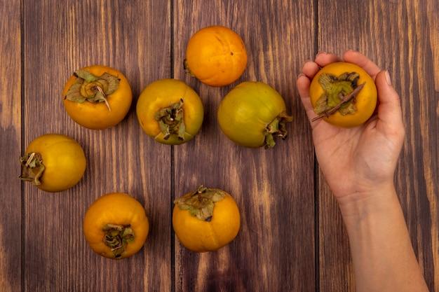 Bovenaanzicht van vrouwelijke hand met een vers oranje kaki fruit op een houten tafel