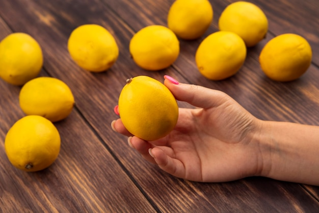 Bovenaanzicht van vrouwelijke hand met een verse citroen op een houten achtergrond