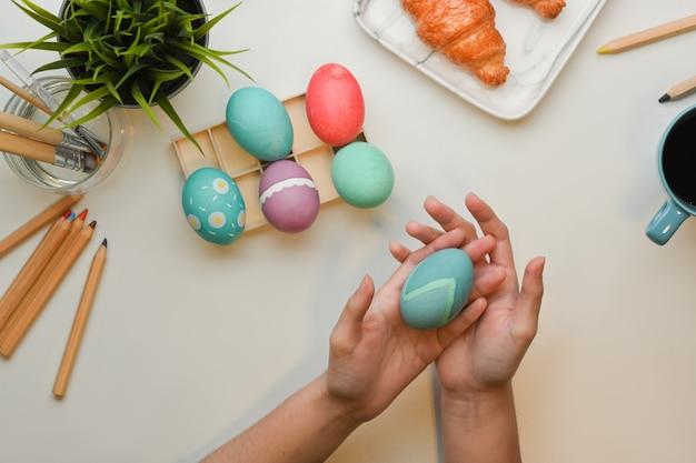 Bovenaanzicht van vrouwelijke hand met ei voor schilderen en het voorbereiden van pasen festival thuis