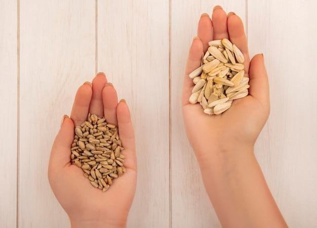 Bovenaanzicht van vrouwelijke hand met in de ene hand smakelijke zoute witte zonnebloempitten en in de andere hand gepelde zonnebloempitten op een beige houten tafel