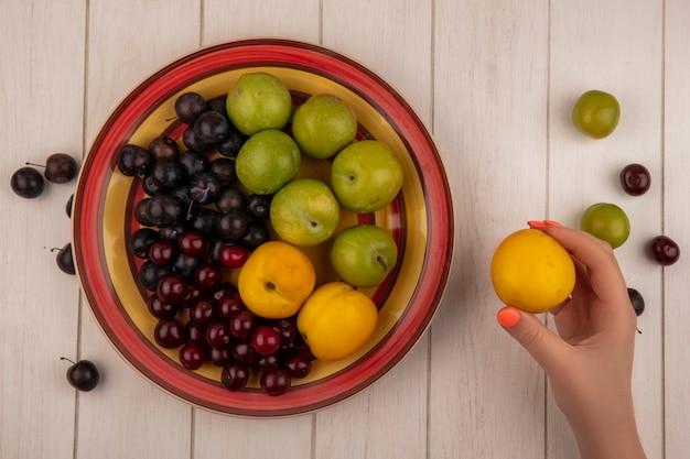 Bovenaanzicht van vrouwelijke hand met perzik met een kom met vers fruit zoals groene kersen pruimen, rode kersen zoete perziken op een witte houten achtergrond