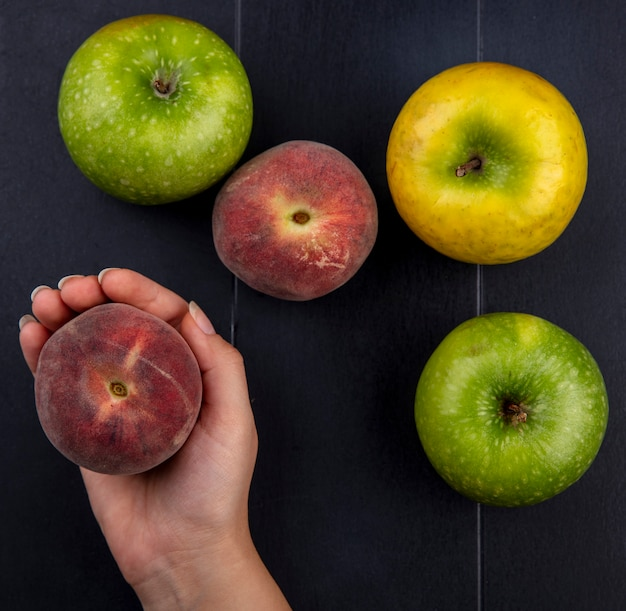 Bovenaanzicht van vrouwelijke hand met perzik met verse en kleurrijke appels op zwart