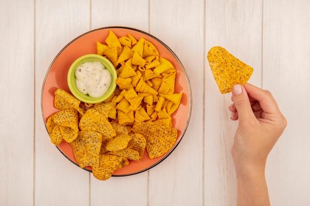Bovenaanzicht van vrouwelijke hand met pittige knapperige chips met een oranje plaat van pittige knapperige chips met saus op een groene kom op een beige houten tafel