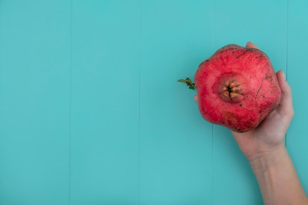 Bovenaanzicht van vrouwelijke hand met rode verse granaatappel op een blauwe achtergrond met kopie ruimte