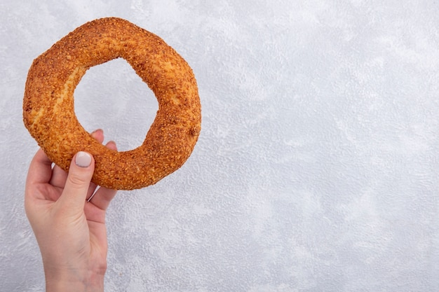 Bovenaanzicht van vrouwelijke hand met sesam turkse bagel op een witte achtergrond met kopie ruimte