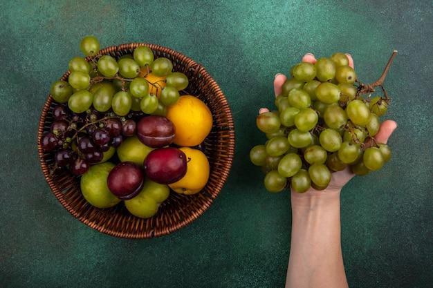 Bovenaanzicht van vrouwelijke hand met tros druiven met mandje van druiven, plukken nectacots op groene achtergrond