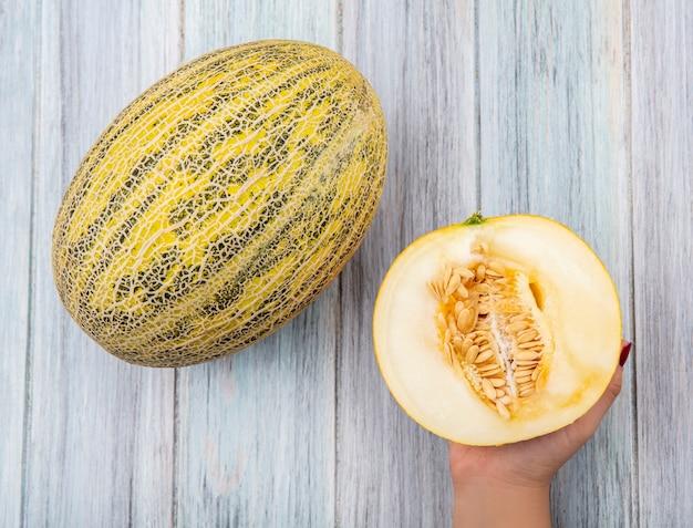 Bovenaanzicht van vrouwelijke hand met verse en heerlijke meloen meloen op grijs hout