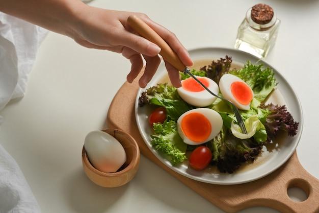 Bovenaanzicht van vrouwelijke hand met vork salade van salade met gekookte eieren, sla en tomaat eten op de eettafel