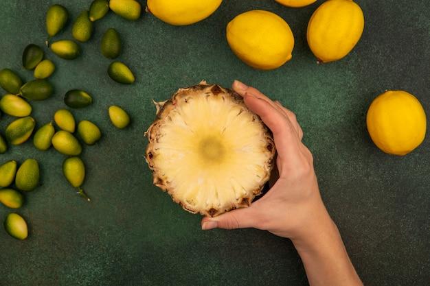 Bovenaanzicht van vrouwelijke hand met zoete halve ananas met citroenen en kinkans geïsoleerd op een groene muur
