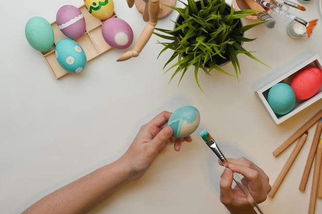 Bovenaanzicht van vrouwelijke hand schilderen op ei pasen festival thuis voorbereiden
