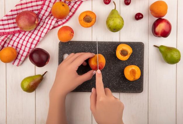 Bovenaanzicht van vrouwelijke handen abrikoos snijden met mes en half gesneden abrikoos op snijplank met patroon van peren, perziken, abrikozen en kersen op geruite doek en op houten achtergrond