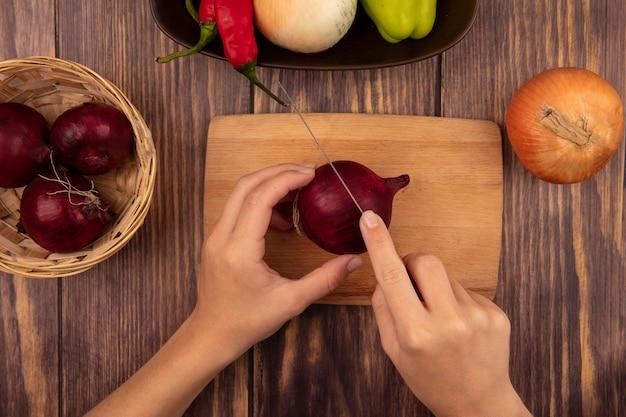 Bovenaanzicht van vrouwelijke handen die een verse rode ui op een houten keukenraad snijden met mes op een houten muur