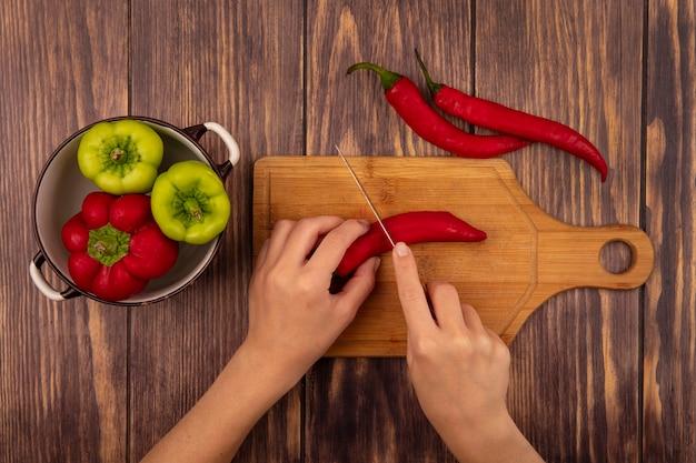 Bovenaanzicht van vrouwelijke handen een chilipeper snijden op een houten keukenbord met mes op een houten muur