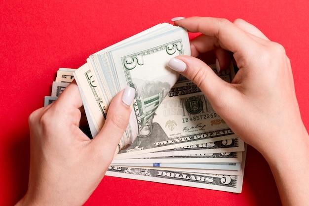 Bovenaanzicht van vrouwelijke handen geld tellen.