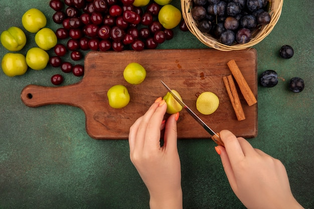 Bovenaanzicht van vrouwelijke handen gesneden groene kersenpruim in stukjes met mes op een houten keuken bord met rode kersen met sleepruimen op een emmer op een groene achtergrond