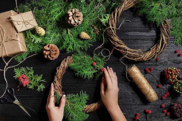 Bovenaanzicht van vrouwelijke handen maken een kerstkrans verpakte geschenken en rollen vuren takken en gereedschap...