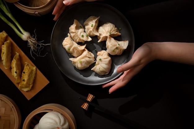 Bovenaanzicht van vrouwelijke handen met een bord dimsum-dumplings om op de eettafel te plaatsen