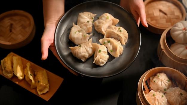 Bovenaanzicht van vrouwelijke handen met een bord met dumplings om te serveren op dimsum tafel in chinees restaurant