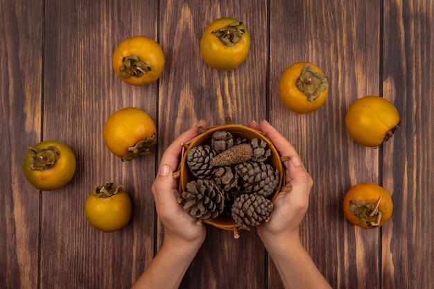 Bovenaanzicht van vrouwelijke handen met een emmer dennenappels met kaki fruit geïsoleerd op een houten tafel