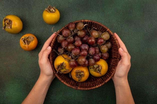 Bovenaanzicht van vrouwelijke handen met een emmer kaki fruit met druiven op een groene achtergrond