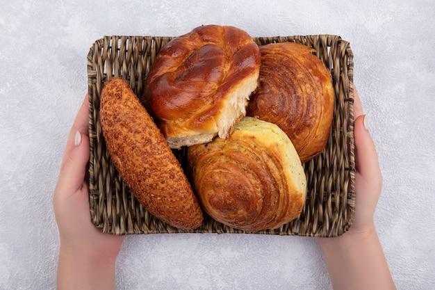 Bovenaanzicht van vrouwelijke handen met een emmer met broodjes zoals sesampasteitje gogal op een witte achtergrond