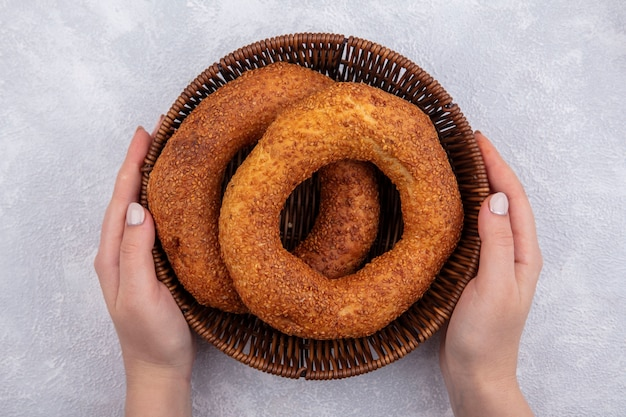 Bovenaanzicht van vrouwelijke handen met een emmer met traditionele turkse bagel op een witte achtergrond