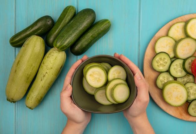 Bovenaanzicht van vrouwelijke handen met een kom gehakte courgettes met komkommers en courgettes geïsoleerd op een blauwe houten oppervlak