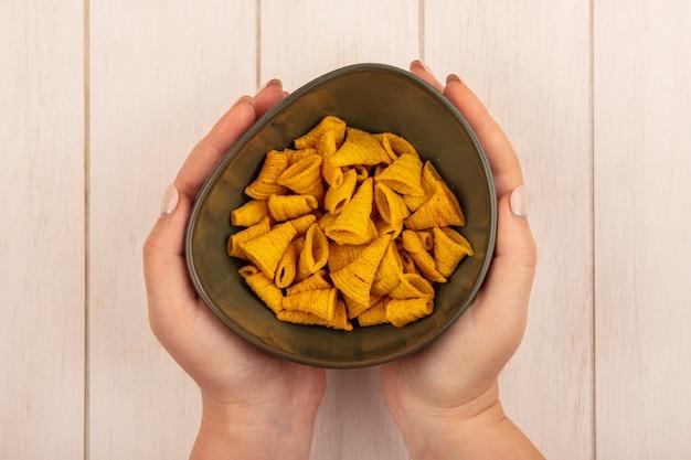 Bovenaanzicht van vrouwelijke handen met een kom kegelvorm maïs snacks op een beige houten tafel