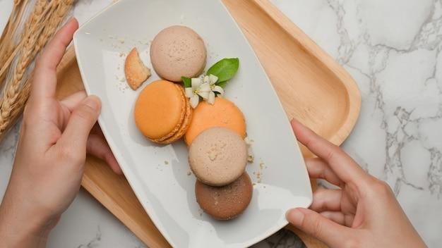 Bovenaanzicht van vrouwelijke handen met een plaat van franse kleurrijke macarons uit houten dienblad te plaatsen op tafel