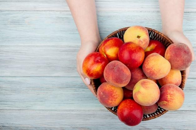 Bovenaanzicht van vrouwelijke handen met een rieten mand met verse rijpe nectarines en perziken op rustiek hout met kopie ruimte