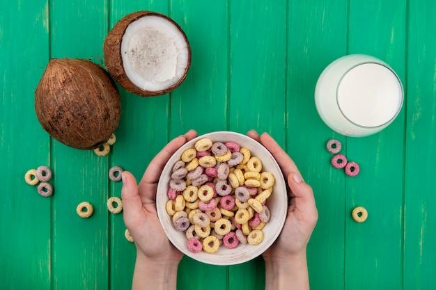 Bovenaanzicht van vrouwelijke handen met granen op witte kom met kokosnoten en een glas melk op groen