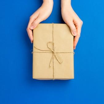 Bovenaanzicht van vrouwelijke handen met huidige doos pakket op blauwe achtergrond.