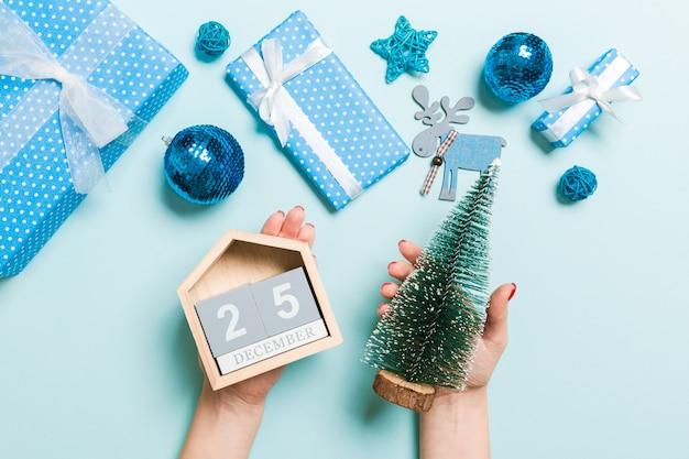 Bovenaanzicht van vrouwelijke handen met kalender op blauwe achtergrond