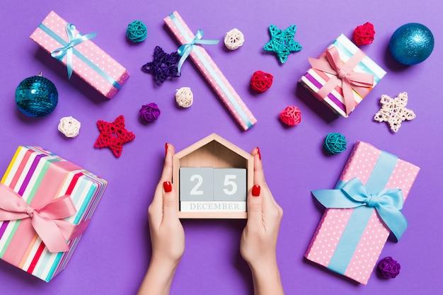 Bovenaanzicht van vrouwelijke handen met kalender op paarse achtergrond