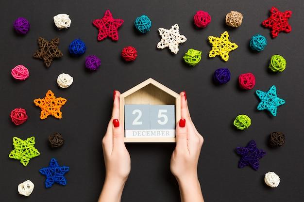 Bovenaanzicht van vrouwelijke handen met kalender op zwarte achtergrond