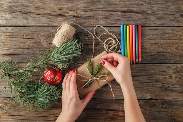 Bovenaanzicht van vrouwelijke handen met kerstcadeau of heden. verpakte geschenken en rollen, vuren takken en gereedschap op armoedige houten tafel. werkplaats voor het voorbereiden van handgemaakte decoraties.