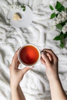 Bovenaanzicht van vrouwelijke handen met kop met hete thee en koekjes op een plaat. witte takken lila op een plaid