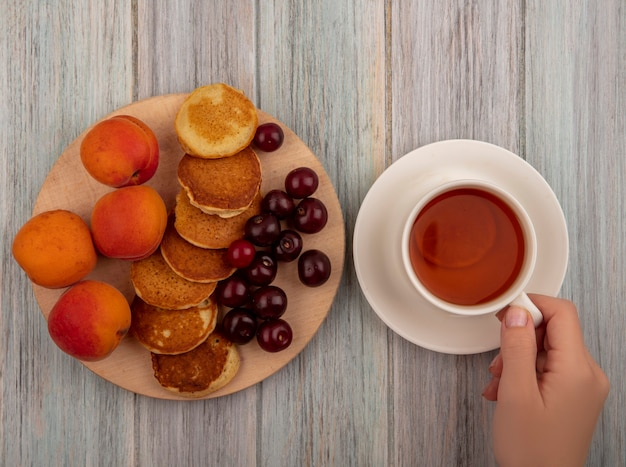 Bovenaanzicht van vrouwelijke handen met kopje thee en pannenkoeken met abrikozen en kersen op snijplank op houten achtergrond