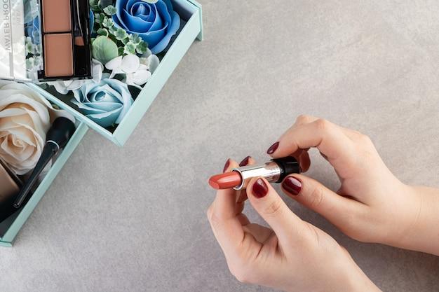 Bovenaanzicht van vrouwelijke handen met lippenstift.