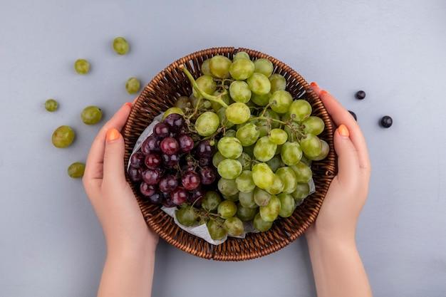 Bovenaanzicht van vrouwelijke handen met mand met druiven met druiven bessen op grijze achtergrond