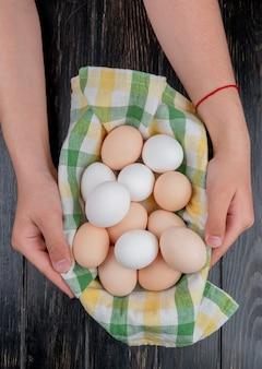 Bovenaanzicht van vrouwelijke handen met meerdere verse eieren op gecontroleerd tafelkleed op houten achtergrond