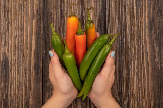 Bovenaanzicht van vrouwelijke handen met verse aromatische paprika's op een houten oppervlak
