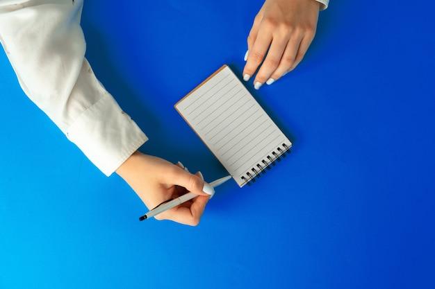 Bovenaanzicht van vrouwelijke handen schrijven in notitieblok op blauwe achtergrond