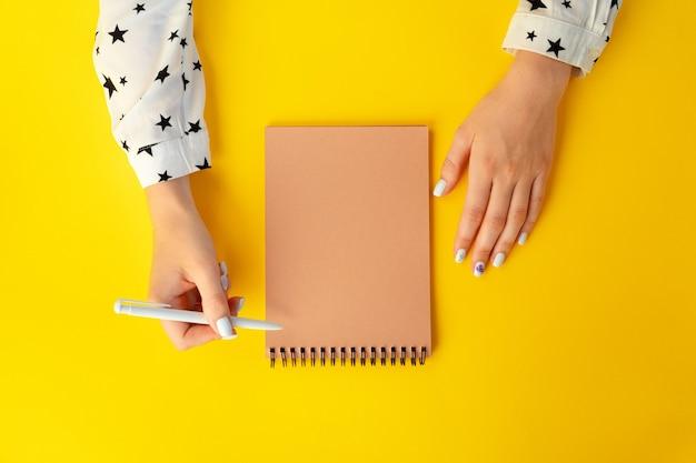 Bovenaanzicht van vrouwelijke handen schrijven in notitieblok