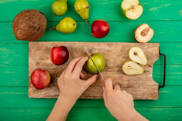 Bovenaanzicht van vrouwelijke handen snijden appel met mes en half gesneden peer en perziken op snijplank met kokos op groene achtergrond