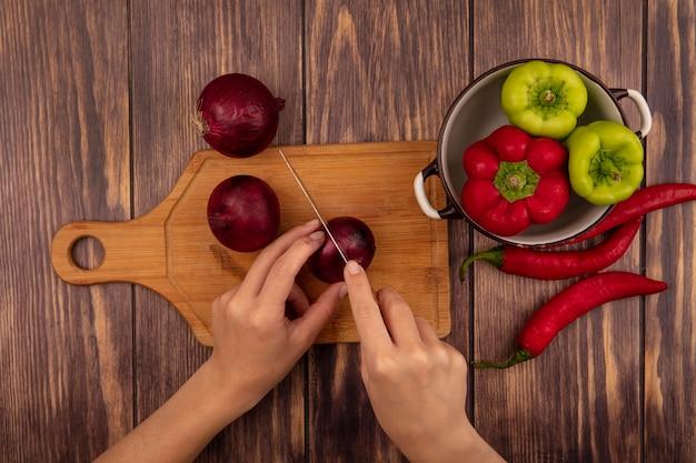Bovenaanzicht van vrouwelijke handen snijden een rode ui op een houten keukenplank met mes met een kom paprika op een houten oppervlak